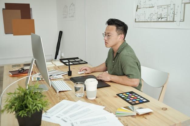 Zajęty młody projektant siedzący przed monitorem komputera