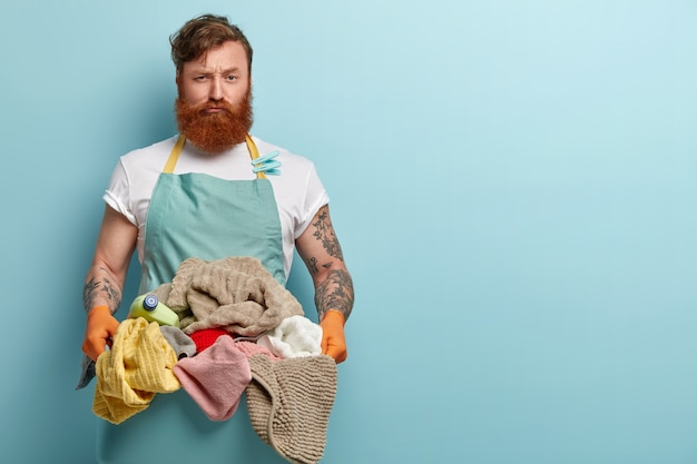 Zajęty niezadowolony rudy mężczyzna niesie umywalkę pełną prania do pralki, zdenerwowany ciężką pracą i obowiązkami domowymi