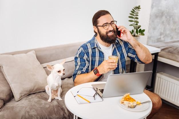 Zajęty, odnoszący sukcesy pracownik zdalny, który uśmiecha się szeroko, rozmawiając przez telefon, siedząc obok pieska
