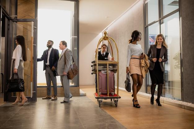 Zajęty portier pchający wózek z bagażem podczas poruszania się wśród ludzi biznesu wchodzących w interakcję na korytarzu hotelu
