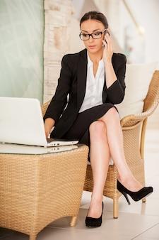 Zajęty pracą. pewna siebie młoda kobieta w stroju formalnym, pracująca na laptopie i rozmawiająca przez telefon komórkowy, siedząc na wygodnym krześle