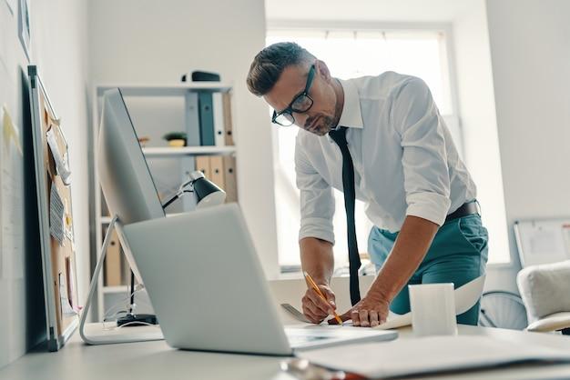 Zajęty pracą. przystojny młody mężczyzna rysujący coś podczas pracy w biurze