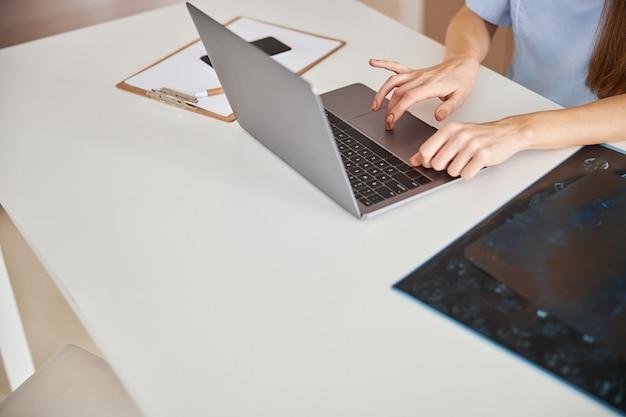 Zajęty pracownik medyczny piszący na laptopie w biurze