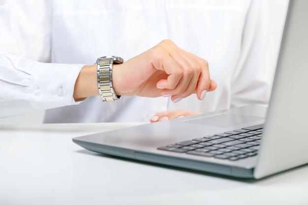 Zajęty punktualny bizneswoman sprawdza czas do terminu, patrzeje zegarek na rękę podczas pracy z laptopem.