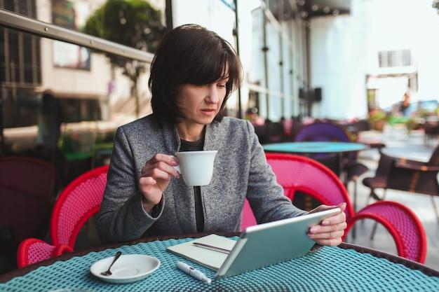 Zajęty spokojny i spokojny biznesmen patrząc na ekran tabletu i popijając herbatę