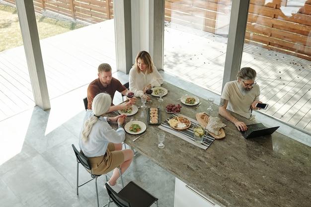 Zajęty starszy brodaty ojciec w okularach za pomocą laptopa i rozmawia przez telefon podczas pracy podczas rodzinnego obiadu