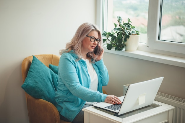 Zajęty starszy kobieta rozmawia przez telefon i pracuje w domu przy laptopie z okularami i blondynem