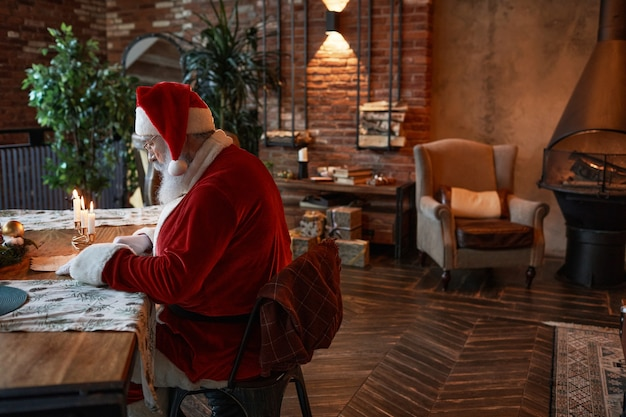 Zajęty święty mikołaj siedzący przy stole i czytający list podczas przygotowań do świątecznej pracy w przytulnym li...