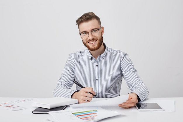 Zajęty, uśmiechnięty, brodaty mężczyzna przedsiębiorca trzyma pióro i dokument