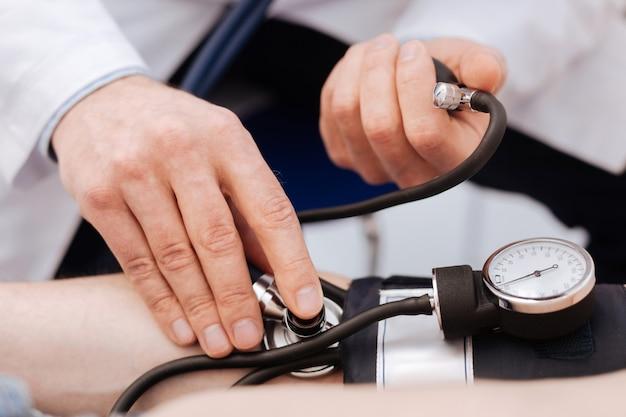 Zajęty wybitny prywatny lekarz przeprowadzający badanie swojego pacjenta przy użyciu specjalnego sprzętu do pomiaru ciśnienia krwi