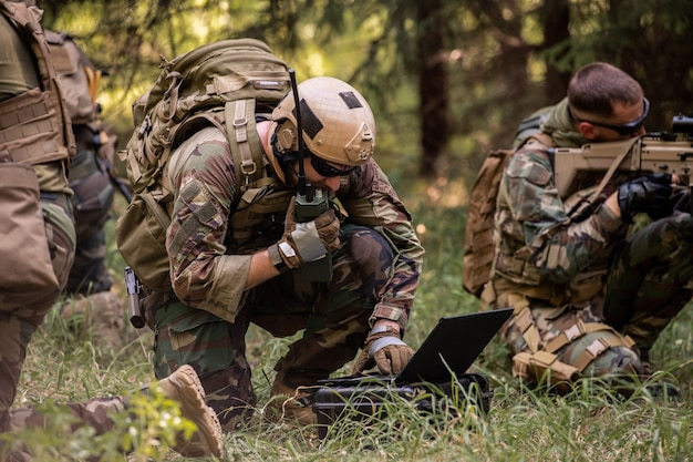 Zajęty żołnierz z plecakiem używający laptopa wojskowego podczas przekazywania informacji przez urządzenie radiowe w lesie