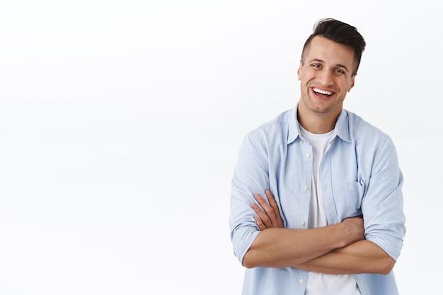 Zajmijmy się prostym biznesem. portret beztroskiego, zrelaksowanego śmiejącego się młodego mężczyzny, skrzyżowane ramiona na klatce piersiowej w gotowej, profesjonalnej pozie, entuzjastyczny, zarządzający własnym małym sklepem, biała ściana