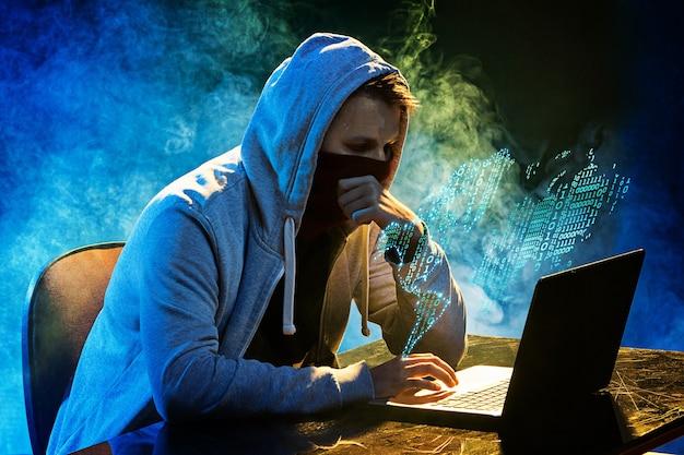 Zakapturzony haker kradnący informacje za pomocą laptopa
