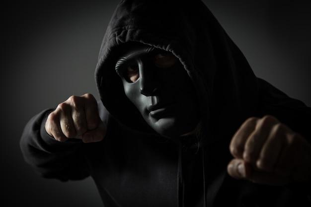 Zakapturzony mężczyzna nie do poznania z zaciśniętymi pięściami