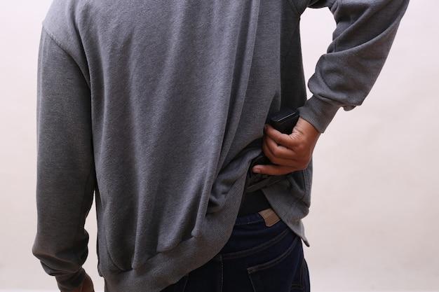Zakapturzony mężczyzna trzymający broń na białym tle
