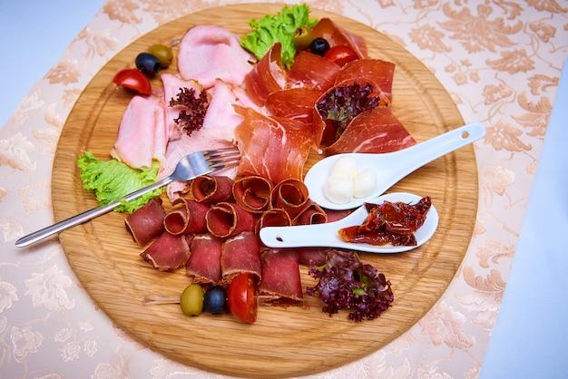 Zakąska mięsna ozdobiona sałatkami, oliwkami i pomidorem