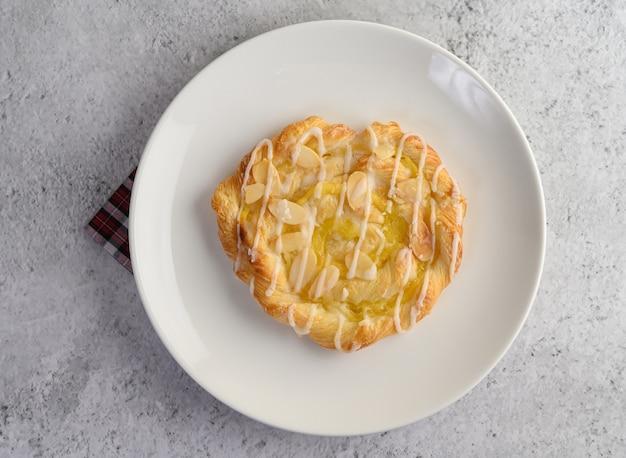 Zakąska migdałowego skręta chleb na białym naczyniu