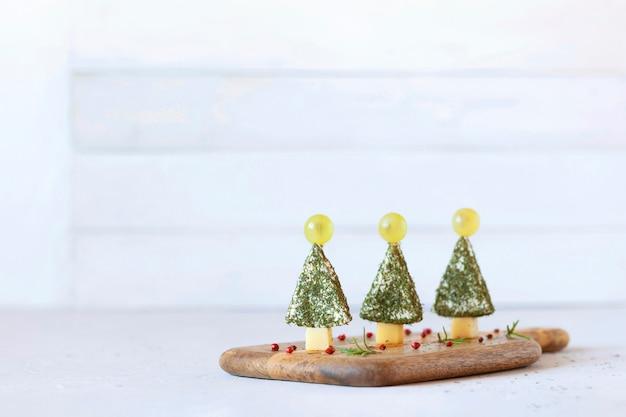 Zakąska noworocznych drzewek z sera i ozdobiona koperkiem i winogronami, łatwe gotowanie, na drewnianej desce do krojenia, widok z boku, miejsce na kopię