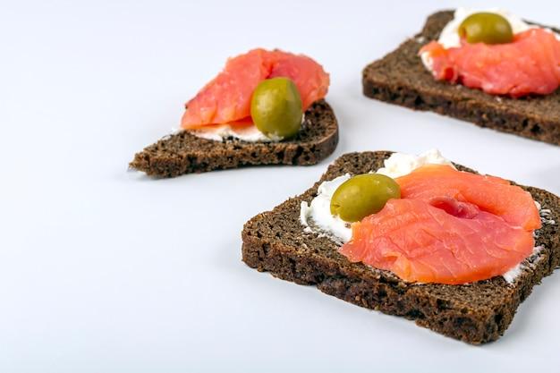 Zakąska, otwarta kanapka z łososiem i miękki ser na białym tle. tradycyjna kuchnia włoska lub skandynawska. pojęcie prawidłowego odżywiania i zdrowego odżywiania. leżał płasko, miejsce na tekst