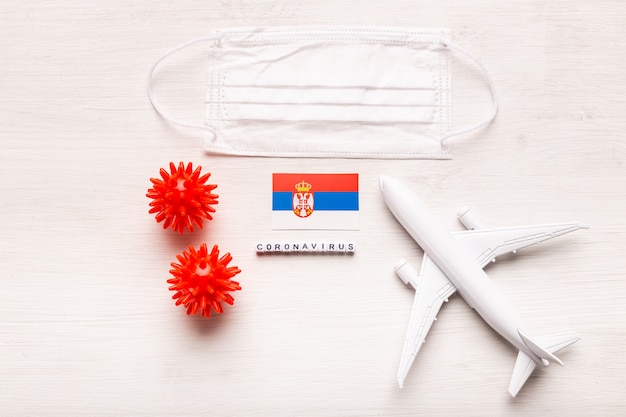 Zakaz lotu i zamknięte granice dla turystów i podróżników z koronawirusem covid-19. samolot i flaga serbii na białym tle. koronawirus pandemia.