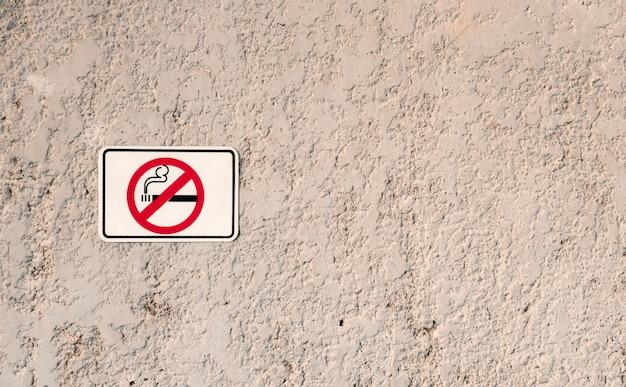 Zakaz palenia biały znak z symbolem papierosa na ścianie z kamienia grunge,