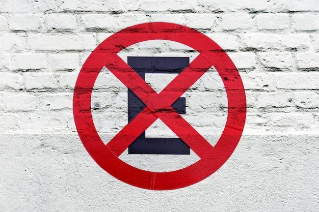 Zakaz parkowania: znak drogowy wybity na białej ścianie, jak graffiti