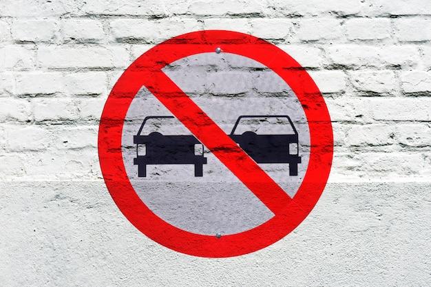 Zakaz wyprzedzania: znak drogowy wybity na białej ścianie, jak grafit