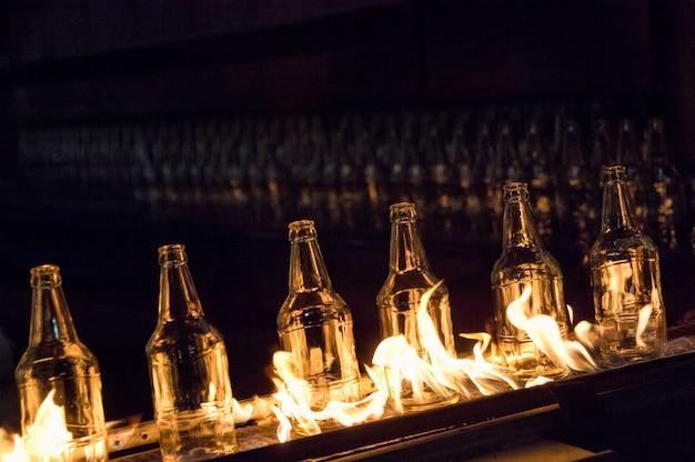 Zakład do produkcji butelek szklanych. szklane butelki na taśmociągu z ogniem