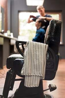 Zakład fryzjerski krzesło z defocused mężczyzna w tle
