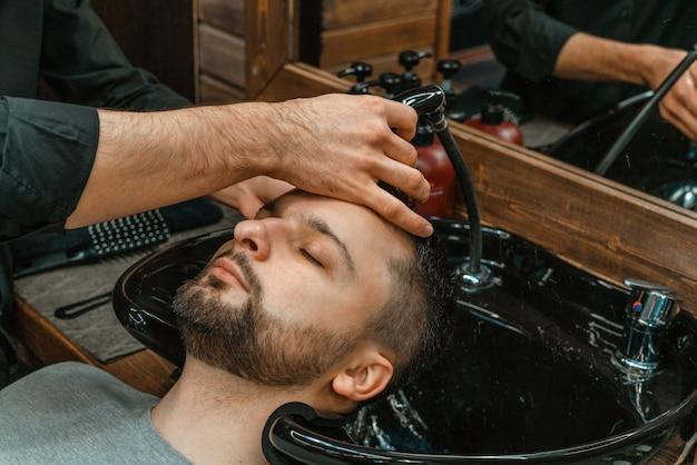Zakład fryzjerski, mężczyzna myje włosy. fryzjer myje swojego klienta. po strzyżeniu umyj włosy i brody. higieny osobistej