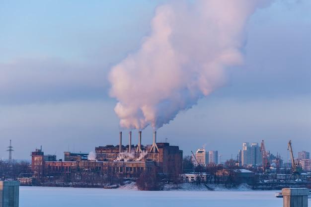 Zakład miejski. zdjęcia pracy produkcyjnej z kłębami dymu w tle miejskich budynków w zimie.