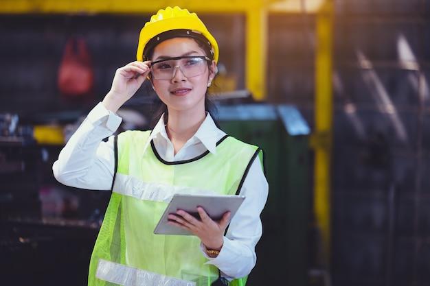 Zakład przemysłowy kobiet z tabletem w dłoni, inżynier przyglądający się pracy przy ustawianiu maszyn przemysłowych w fabryce.