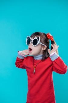 Zakładanie fajnych okularów. aktywny zszokowany dziewczynka ubrana w białe okulary dla dorosłych i podnosząc ręce