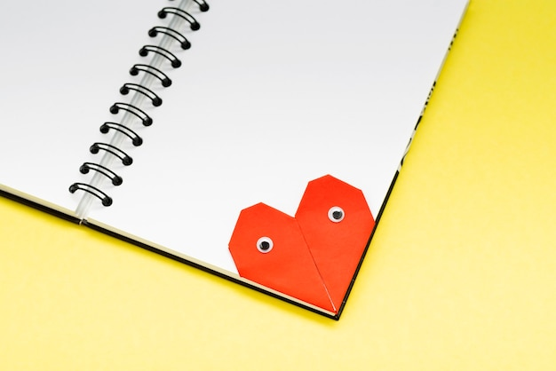 Zakładka serce z oczami do książki na żółtym tle z bliska.
