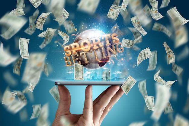 Zakłady sportowe online. dolary spadają na tle dłoni ze smartfonem i piłką nożną. kreatywne tło, hazard.