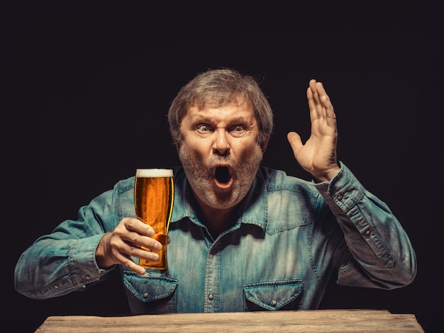 Zaklęty i emocjonalny fan ze szklanką piwa
