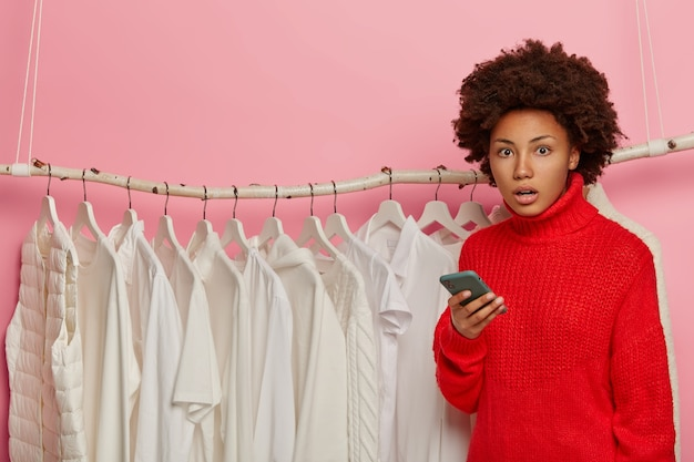 Zakłopotana afroamerykanka używa telefonu komórkowego do zakupów, pozuje w sklepie odzieżowym, nosi czerwony sweter, pozuje blisko stojaka z białymi ubraniami