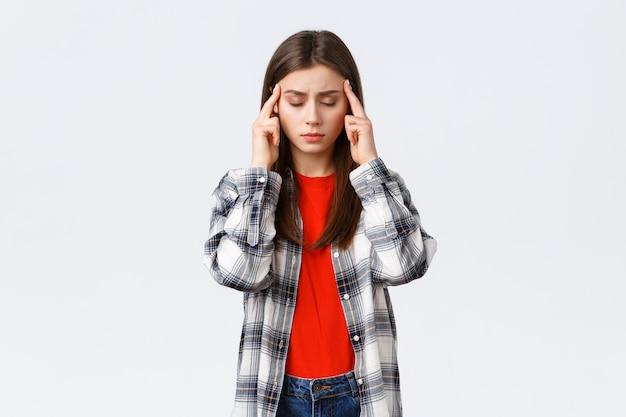 Zakłopotana i wyczerpana młoda studentka próbuje skupić się, czuje ból głowy lub zawroty głowy, zamyka oczy i pociera świątynie, białe tło
