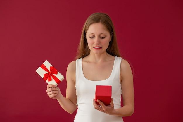 Zakłopotana kobieta patrząc na prezent na czerwonym tle