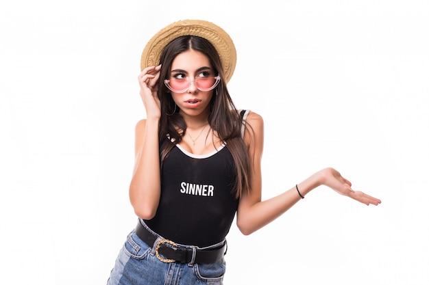 Zakłopotana kobieta z szelkami w lekkiej słomce nosi przezroczyste okulary przeciwsłoneczne