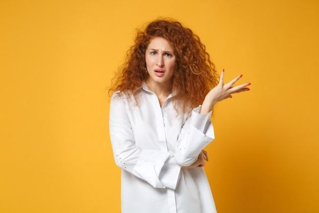 Zakłopotana młoda ruda kobieta dziewczyna w białej koszuli pozuje na białym tle na żółtopomarańczowej ścianie