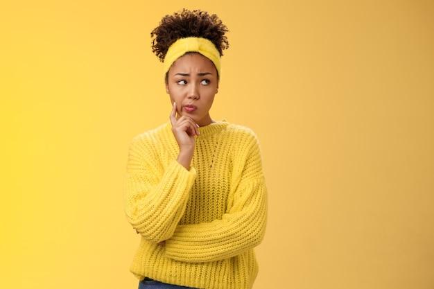 Zakłopotana niepewna śliczna nieśmiała afro-amerykańska kobieta myśląca jak uciec niezręcznej sytuacji uśmiechnięta marszcząca brwi zaniepokojona dotyk policzek zamyślona myślenie nerwowo, zmartwiona żółtym tle.