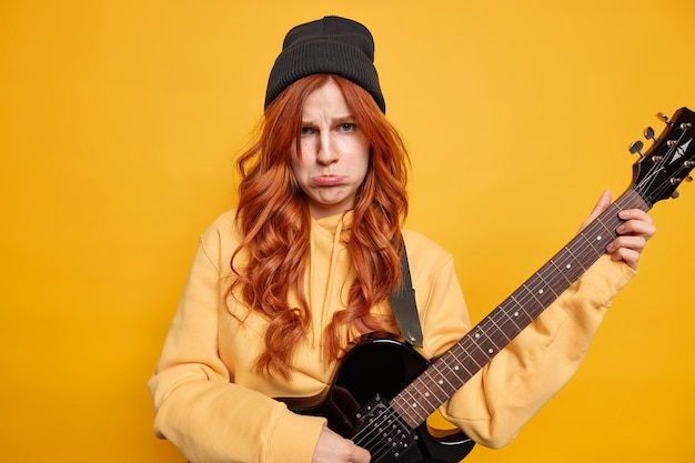 Zakłopotana nieszczęśliwa ruda młoda kobieta gra na gitarze elektrycznej basowej, ma smutny wyraz twarzy, nosi czarny kapelusz i casualową żółtą bluzę pozuje w pomieszczeniu. niezadowolony rocker z instrumentem muzycznym