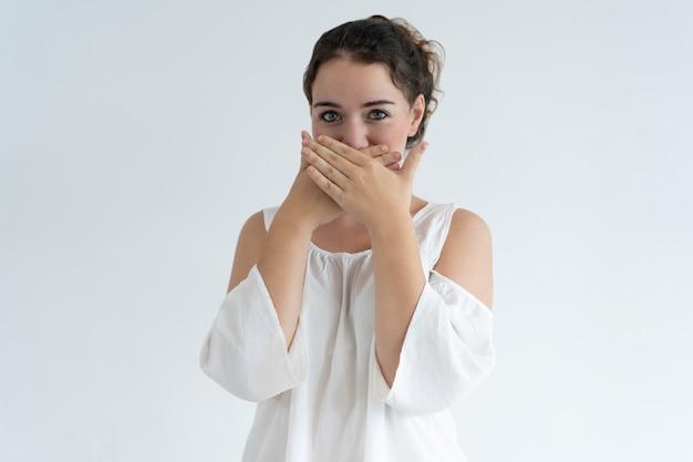 Zakłopotana urocza dama zakrywa usta z rękami