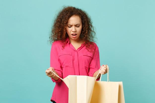 Zakłopotany afryki dziewczyna w różowe ubrania dorywczo trzymać pakiet torba z zakupami po zakupach na białym tle na tle niebieskiej ściany turkus. koncepcja życia szczere emocje ludzi. makieta miejsca na kopię.