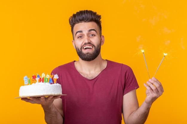 Zakłopotany młody mężczyzna hipster z brodą, trzymając w rękach tort urodzinowy i patrząc w zamyśleniu na niego pozowanie na żółtym tle. pojęcie czasu szybko mija.