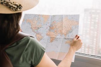 Zakończenie żeński turystyczny czytanie mapa blisko okno