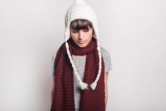 Zakończenie chora kobieta jest ubranym białego zwełnionego kapeluszowego patrzeć w dół przeciw białemu tłu