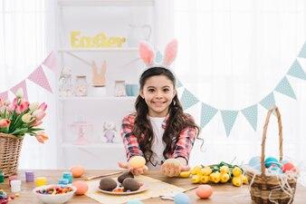 Zakończenie uśmiechnięta dziewczyna jest ubranym królików ucho pokazuje kolorowych Easter jajka