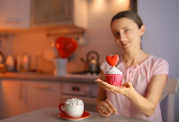 Zakochana dziewczyna przygotowuje babeczki dla ukochanej osoby na walentynki, dekorując deser sercem. piękne i pyszne wyznanie miłości.